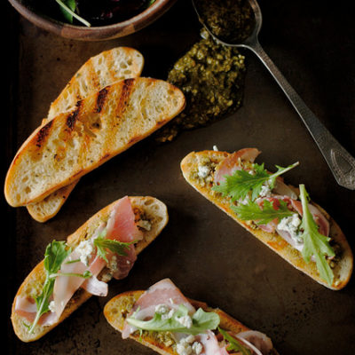 Pancetta, Blue Cheese, Pesto, and Arugula Crostini