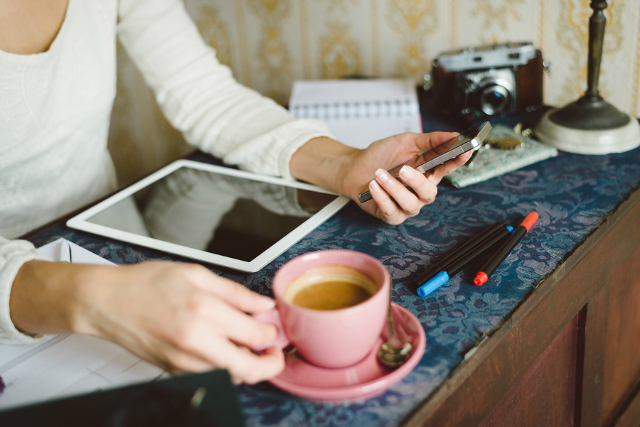 Working at home concept. Entrepeneur business woman checking email or messaging on smartphone and drinking coffee.