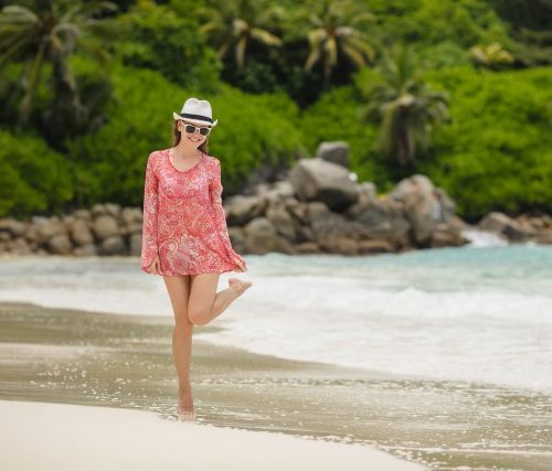 Slender young brunette woman with long straight hair, beautiful figure, a gentle smile, wearing sun glasses, barefoot, wearing a short red-white summer dress, white hat, spending time on the beautiful tropical beach, enjoying the ocean and nature