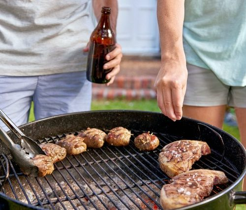Women seasoning meat on outdoor garden barbecue while man turns meat