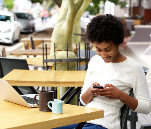 Portrait of african woman using mobile phone at an outdoor cafe with laptop and cup of coffee on table ** Note: Visible grain at 100%, best at smaller sizes