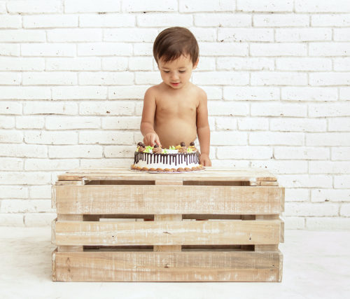 full view portrait of handsome toddler playing with his cake
